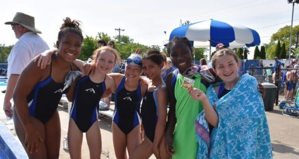 Six girls swim team members on the pool deck