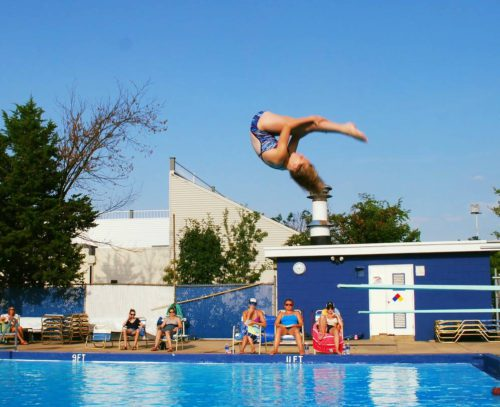 West side diver doing a forward flip in the pike position during a meet